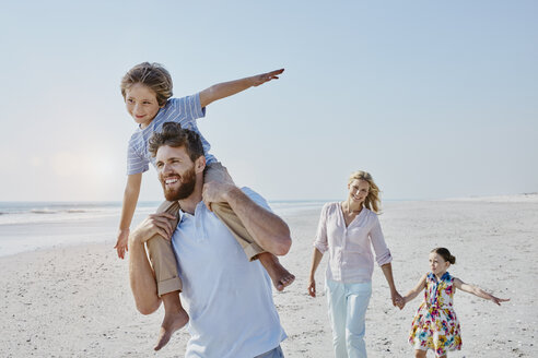 Happy family strolling on the beach - RORF00769