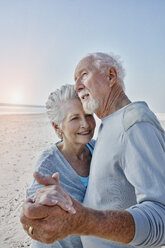 Happy senior couple dancing on the beach - RORF00781