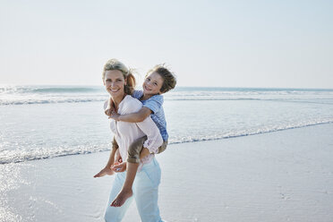 Happy mother carrying son piggyback on the beach - RORF00787