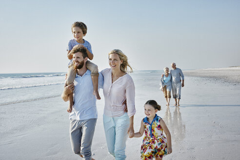 Happy extended family strolling on the beach - RORF00790