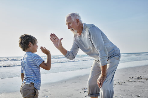 Grandfather and grandson high fiving on the beach - RORF00793