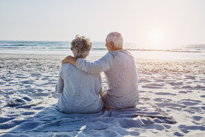 Senior couple sitting on the beach looking at distance - RORF00799
