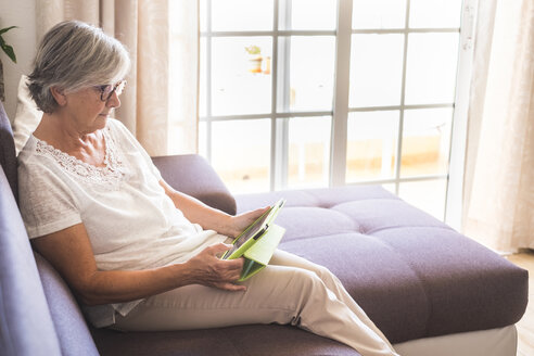Senior woman sitting on the couch using tablet - SIPF01632