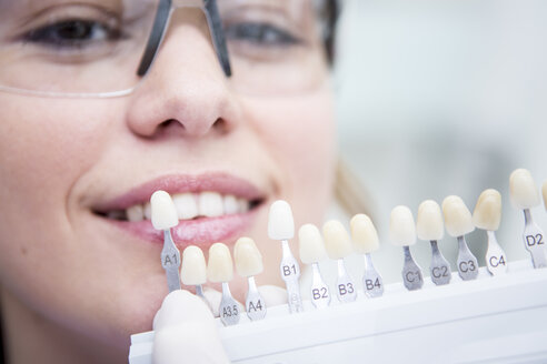 Woman at the dentist choosing color for teeth whitening - WESTF22935