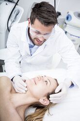 Aesthetic surgery, doctor looking at woman - WESTF22977