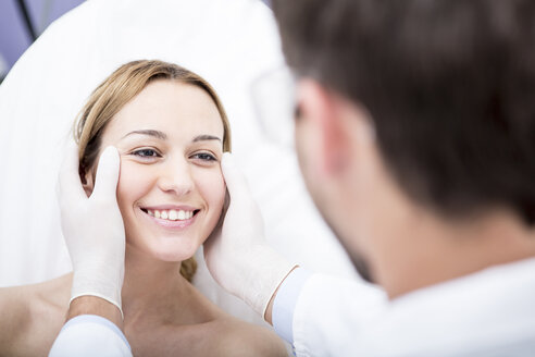 Aesthetic surgery, doctor looking at woman - WESTF22980