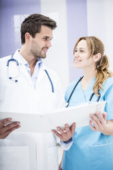 Two smiling doctors holding folder - WESTF22983