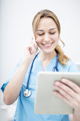 Smiling doctor on the phone looking at tablet - WESTF22989