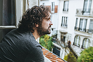Man looking through opened window at home - KIJF01442