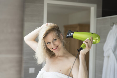 Portrait of smiling blond woman using hair dryer in the bathroom - CHPF00393