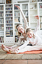 Mother and daughter doing gymnastics at home - WESTF22998