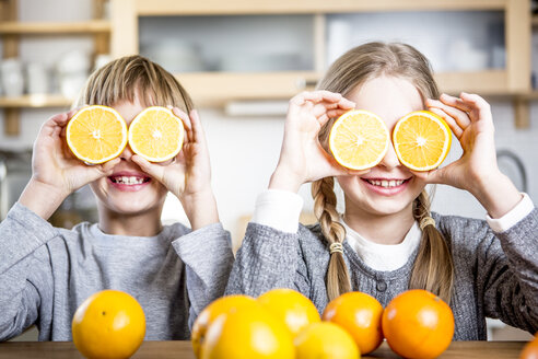 Brother and sister covering their eyes with slices of oranges - WESTF23010