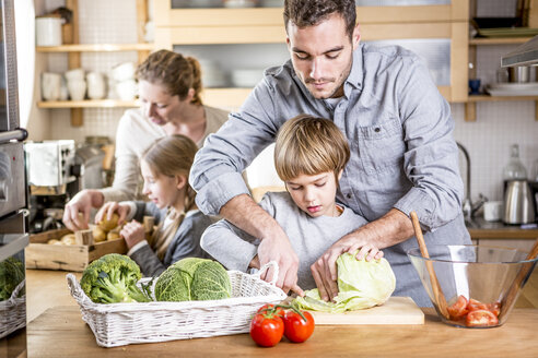 Family preparing salad in kitchen - WESTF23016