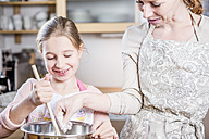 Mother and daughter baking in kitchen together - WESTF23058