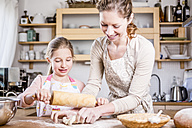Mother and daughter baking in kitchen together - WESTF23061