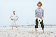 Portrait of smiling little boy playing with his father on the beach - MVCF00156