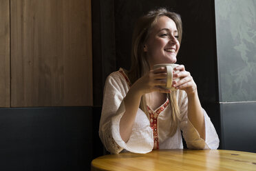 Portrait of smiling woman with cup of coffee in a coffee shop - ABZF01968