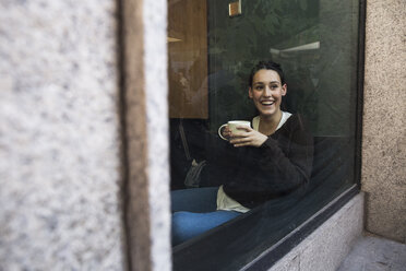 Portrait of smiling woman with cup of coffee sitting behind windowpane in a coffee shop - ABZF01971