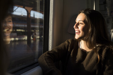 Happy young woman on a train looking out of window - ABZF01977