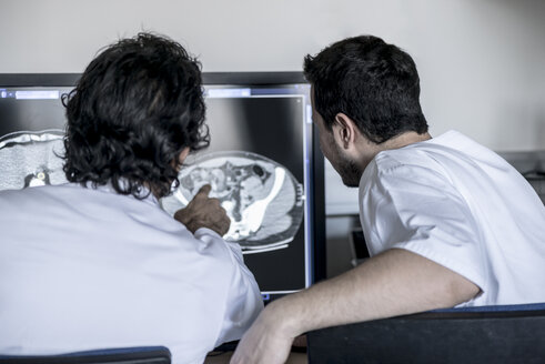 Two doctors discussing x-ray image on computer screen - MWEF00156