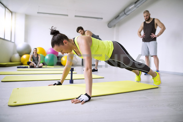 Woman exercising in gym watched by training partners - HAPF01609