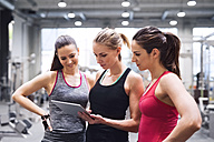 Three women with tablet after exercising in gym - HAPF01615