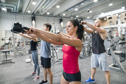 Group of athletes exercising with kettlebells in gym - HAPF01627