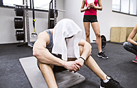 Exhausted athlete with towel on his head after exercising in gym - HAPF01636