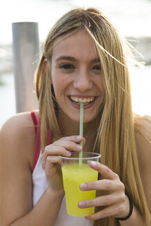 Laughing young woman with yellow beverage - KKAF00727