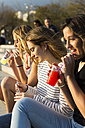 Three young women with soft drinks at sunset - KKAF00730