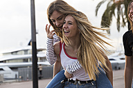 Laughing young woman giving her friend a piggyback ride - KKAF00733