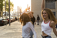 Three friends dancing on sidewalk - KKAF00736