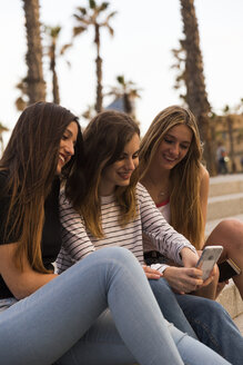 Three smiling young women sitting on stairs looking at cell phone - KKAF00739