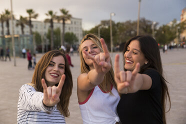 Spain, Barcelona, three happy young women showing Rock And Roll Sign - KKAF00742
