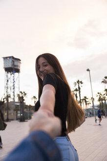 Spain, Barcelona, happy young woman holding hand - KKAF00748