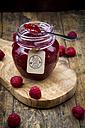 Spoon and jar of raspberry jam and raspberries on wood - LVF06066
