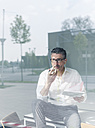 Portrait of businessman behind windowpane using cell phone and earphones in an office - UUF10496