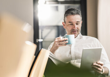 Portrait of businessman with cup of coffee sitting in his office using tablet - UUF10502