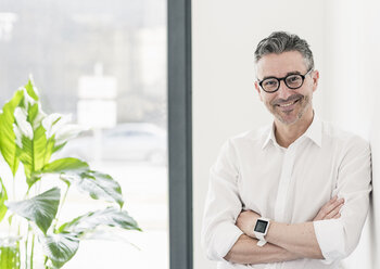 Portrait of smiling businessman wearing smartwatch and glasses - UUF10505