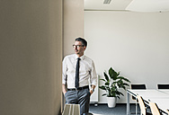 Businessman standing in conference room looking through window - UUF10508