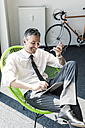 Smiling businessman sitting in an armchair using tablet, smartphone and earphones - UUF10514