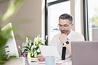 Businessman working at desk in his office - UUF10517