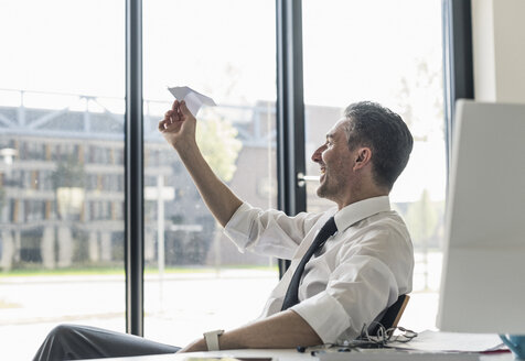 Smiling businessman sitting at desk in his office looking at paper plane - UUF10526