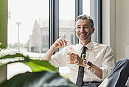Happy businessman blowing soap bubbles in his office - UUF10529