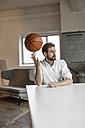 Portrait of pensive young businessman sitting at table in a loft balancing basketball on his finger - JOSF00731
