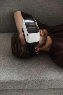 Man lying on the couch using Virtual Reality Glasses - JOSF00755