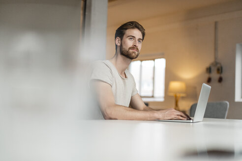 Portrait of young man working on laptop in a loft - JOSF00758