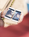 Hands holding smart phones with pictures of a young couple - UUF10531