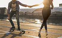 Young couple skateboarding at the riverside - UUF10537