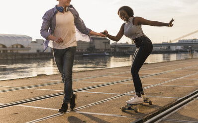 Young couple skateboarding at the riverside - UUF10540